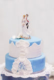 Wedding cake in soft blue and white, with bride and groom figure Stock Photos