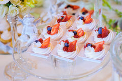 Wedding cake with strawberries. On a plate in a sculpture of an angel stock photo