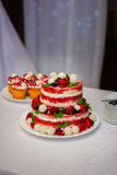 Wedding cake with strawberry. Wedding cake on a table with a wild strawberry and berries Stock Photos
