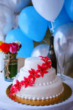 Wedding cake table arrangement. Vertical shot of a wedding reception table setup with elegant wedding cake, roses bouquet and blue and white balloons Royalty Free Stock Image