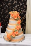 Wedding cake. Tall wedding cake decorated with natural orange roses and greenery stock image