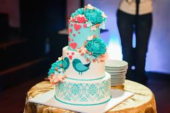 Wedding cake with three tiers of white blue glaze decorated with flowers and hearts. On the table Stock Image