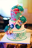Wedding cake with three tiers of white blue glaze. Large wedding cake with three tiers of white blue glaze decorated with flowers and hearts on the table Stock Images
