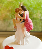 Wedding Cake Topper Depicting One Man with Several Women. Wedding cake topper with several women and one man representing non- monogamy, polyamory, polygamy or a stock images