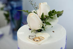 Wedding cake and topper with wedding rings Stock Photos