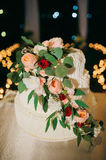 Wedding cake. Decorated with roses and leaves on a dark background with bokeh from candles stock images
