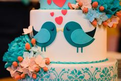 Wedding cake of white blue glaze decorated with flowers and hearts Stock Photography