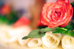 Wedding cake with white chocolate rose and spirals. Homemade chocolate decorations in shallow depth of field and soft focus Royalty Free Stock Photos