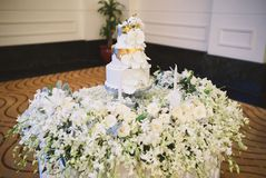 Wedding cake and white flower petals decoration on the table royalty free stock photography