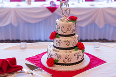 Wedding cake. White wedding Cake with red roses and ribbons stock images