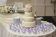 Wedding cake. White wedding cake on a table with gifts royalty free stock photography