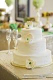 Wedding cake. A white three tiered wedding cake with white flowers royalty free stock image
