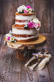 Wedding cake on wooden cut stand. Homemade wedding naked cake decorated with flowers on wooden cut stand Stock Image