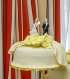 Wedding cake with yellow roses and figurines Royalty Free Stock Images