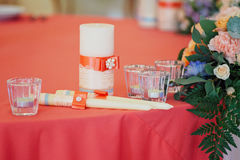 Wedding candles decorated with bow and ribbons. Wedding candles decorated with bow, lace and ribbons, and bouquet near them, on red tablecloth Stock Photos