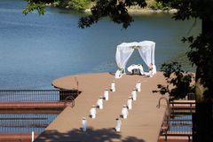 Wedding canopy. The canopy on the raft prepared for a wedding with bouquets of flowers in front of, on white pedestal stock photo