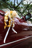 Wedding car. Red wedding car with roses bouquet tied on the door handle Stock Photos