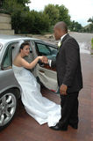 Wedding Car. Groom helping his bride out of the car used to transport them from wedding to reception to hotel Stock Images