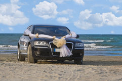 Wedding car. On a beach with a beautiful sky in the background and running bride reflection on the car's body Royalty Free Stock Images