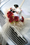 Wedding car with bear. Silver wedding car with bridal bear and roses bouquet Royalty Free Stock Photo