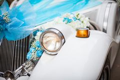 Wedding car with beautiful decorations. Close up white and cyan flowers roses on newlyweds car.  stock photo
