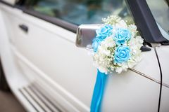 Wedding car with beautiful decorations. Close up white and cyan flowers roses on newlyweds car.  royalty free stock photography