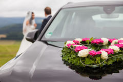 Wedding car with bride and groom in the background royalty free stock image