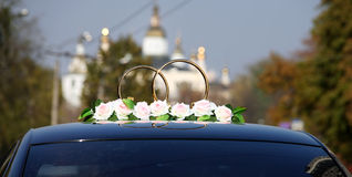 Wedding car decorated with rings bells and flowers Stock Image