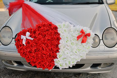 Wedding car decorated with two hearts made ��of flowers Stock Photos