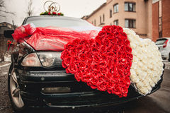 Wedding car decorated with two hearts made of Stock Photos