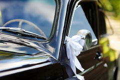 Wedding car decorated with white ribbons Royalty Free Stock Images
