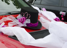 Wedding car decoration. Black hat and bow decoration on a red wedding car Royalty Free Stock Photography