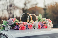 Wedding car decoration with flowers and golden rings Royalty Free Stock Images
