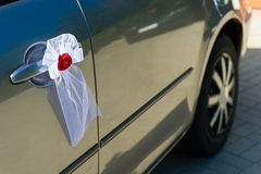 Wedding car door decoration. Red flower with a white ribbon. Decoration on a wedding car door Royalty Free Stock Photos