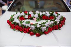 Wedding car and petals on top. Luxury wedding car decorated with flowers.just married sign and cans attached. Heart roses royalty free stock images