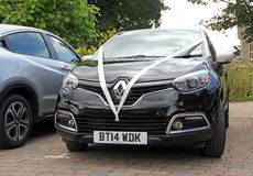 Wedding car. Photo of a black renault wedding car with white silk ribbons attending whitstable castle grounds on 16th july 2016 Stock Photography