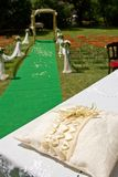 Wedding carpet. Wedding ring on pillow and wedding arch with carpet, green Royalty Free Stock Image