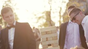 Wedding celebration, a bridegroom in an elegant black wedding costume, white shirt and bow tie playing jenga with his stock video