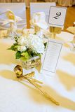 Wedding Centerpiece and Menu. Wedding centerpiece with banquet menu with gold serving spoons Stock Photography