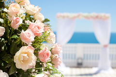 Wedding ceremony. Wedding with arch and sea in background. Focus on a bouquet of roses Royalty Free Stock Photos