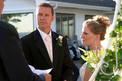 Wedding ceremony. Attractive Caucasian bride and groom exchanging wedding vows during an outside ceremony Stock Image
