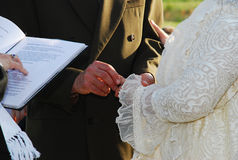 Wedding ceremony. Close up of groom putting wedding ring on brides finger, priest with open prayer book in foreground Royalty Free Stock Image