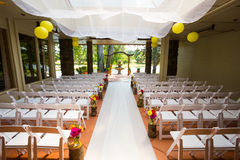 Wedding Ceremony Aisle Seating. White chairs and rows of seating create a nice venue for the bride to walk down the aisle at this wedding ceremony stock photo