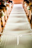 Wedding Ceremony aisle. White ribbon tied in a bow at the front of a aisle runner at a wedding royalty free stock photography
