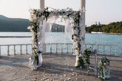 Wedding ceremony arch it the beautiful lake place. Details of decoration.  Stock Photos
