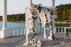 Wedding ceremony arch it the beautiful lake place. Details of decoration.  Stock Photo