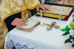 Wedding ceremony attributes in church. Priest holds his hands on the wedding ceremonial attributes on the altar in a church Royalty Free Stock Photo
