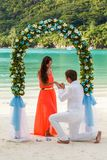 Wedding ceremony on the beach. Young newly married couple and wedding ceremony on the beach, the details of design, bouquet of frangipani, Seychelles Stock Photos