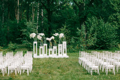 wedding ceremony in a beautiful garden. white chairs and mirrored tables. Glass vase with flowers calla lilies   amaryllis Stock Image