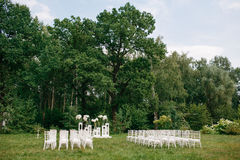 wedding ceremony in a beautiful garden. white chairs and mirrored tables. Glass vase with flowers calla lilies amaryllis Stock Photos